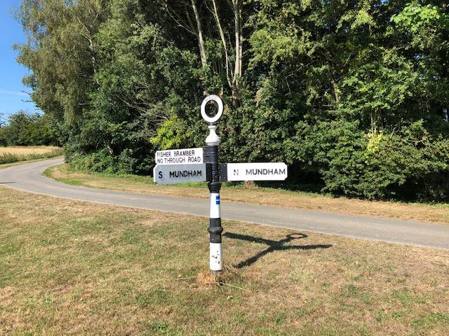 traditional black and white finger post sign providing directions to South Mundham, North Mundham and Fisher